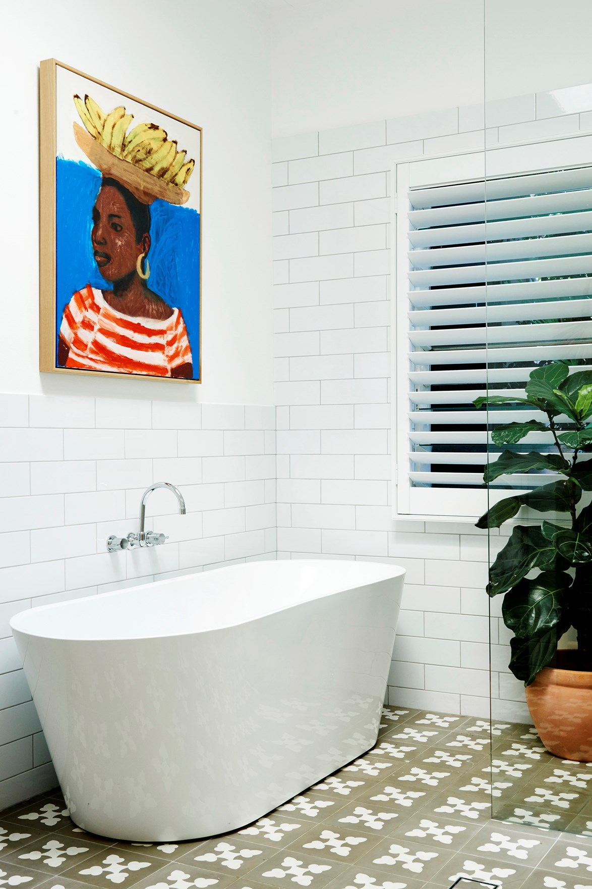 "This main bathroom is visible from the hallway so the owner of this [colourful coastal home](https://www.homestolove.com.au/coastal-cottage-byron-bay-20442|target=""_blank"") wanted it to have some personality. A bathtub from Highgrove Bathrooms, Jatana floor tiles and an Emma Gale artwork tick that box!"