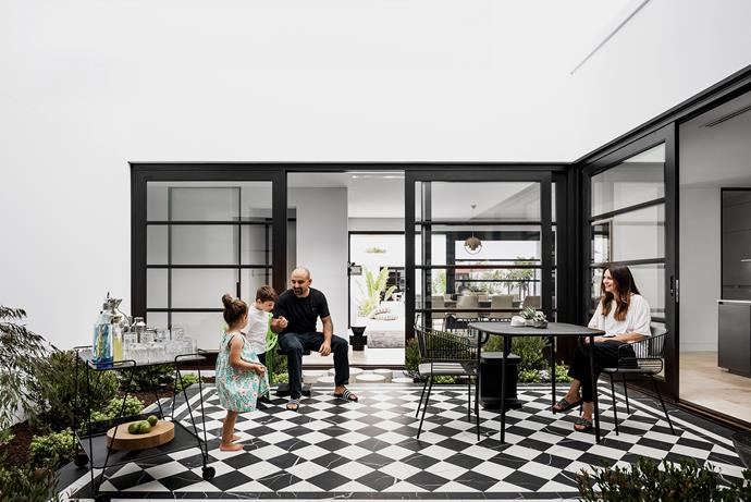 """It's a beautiful space that we all enjoy,"" says Lucia, pictured with her husband Andrea and their children Angelo and Valentina. ""It's wonderful for imaginative play – the children are always finding gnomes, fairies and frogs among the plants."" Outdoor setting, Ultimo. Cocktail accessories, Table Culture and Living Edge. Matte Marmo tiles, Myaree Ceramics. Landscaping by Aneura Gardens & Flowers."