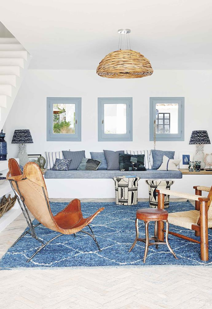 "**Living area** An abundance of soft, blue-toned cushions takes this built-in sofa into the 'comfort' zone. The woven chair is vintage Mexican. Both pineapple table lamps are converted vases. Leather butterfly chair, stools and Berber rug, [HZI](http://www.hzinteriors.com/|target=""_blank""
