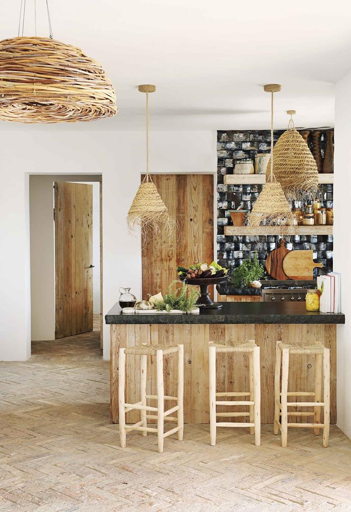 "**Kitchen** Black slate benchtops look great with the reclaimed timber cupboards and seagrass pendant lights bought through [HZI](http://www.hzinteriors.com/|target=""_blank""