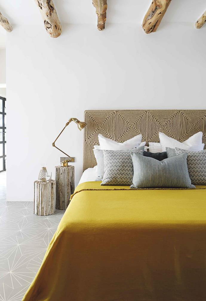 **Main bedroom** Deborah and Tom didn't want a traditional bedhead so Hubert had this striking rope design made for the couple. Dandelion floor tiles in Stone Grey from Marrakech Design. Fermoie fabric cushions. Yellow linen throw, Once Milano.
