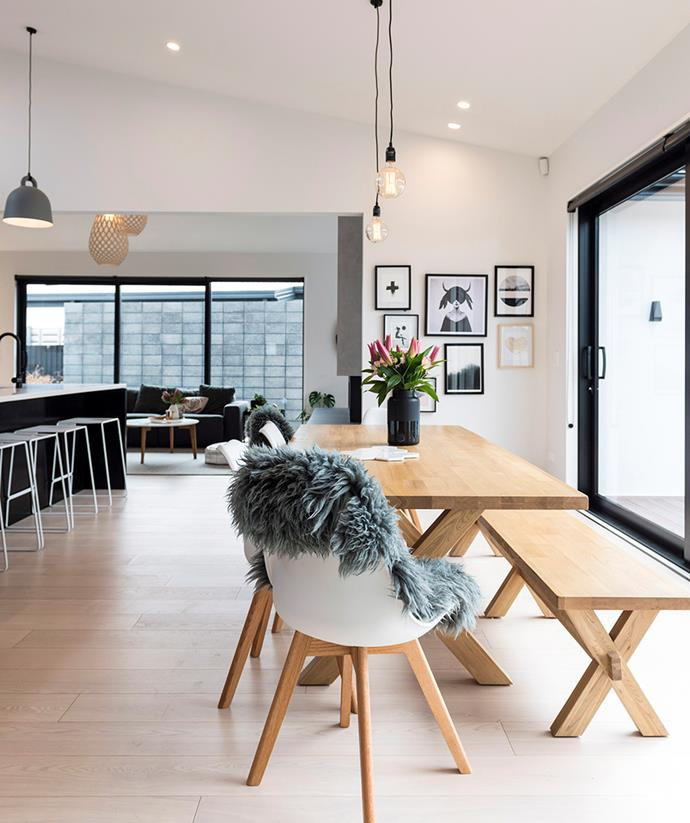 This open-plan kitchen and dining area uses the perfect blend of natural lighting, downlights and pendant lamps. *Image: Kate Claridge / bauersyndication.com.au*