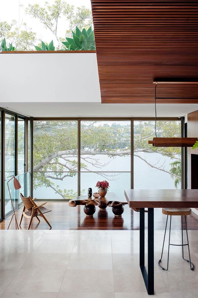 This waterfront home designed by TKD Architects embraces the Japanese-Australian heritage of the owners, as well as their love of Bali. The living room is down a couple of steps from the kitchen and features a Hans J. Wegner 'CH28' chair and Gubi 'Grasshopper' lamp, both from Cult. The timber table was custom made in Byron Bay. From *Belle* April 2016.
