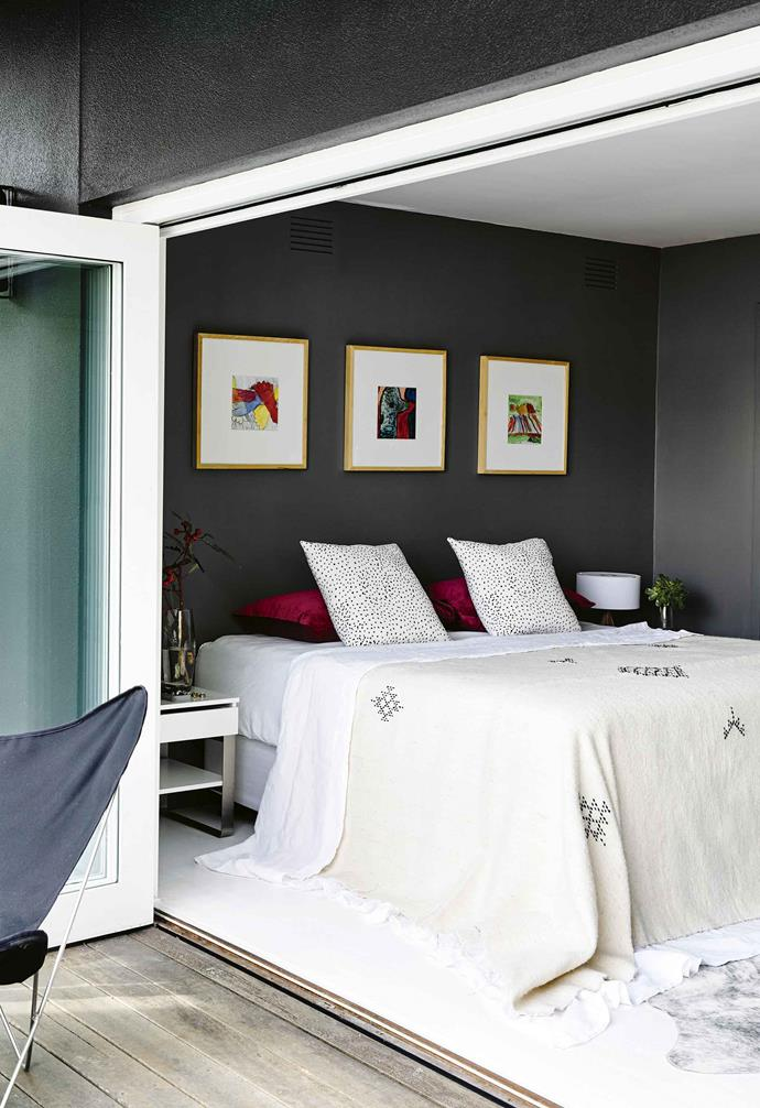 "Black, white and timber are at the heart of Helen's colour scheme, with a series of dark [feature walls](https://www.homestolove.com.au/how-to-paint-a-feature-wall-7936|target=""_blank"") used to create contrast and direct the eye. Statement pieces, such as the custom bus scroll in the living area and beaded Weylandts chandelier over the dining table, add texture and interest.<br><br>**Master bedroom** The artworks above the bed hold special meaning for Helen and Peter. ""They're by our talented son when he was about six years old – one is a traced outline of his foot!"" says Helen."