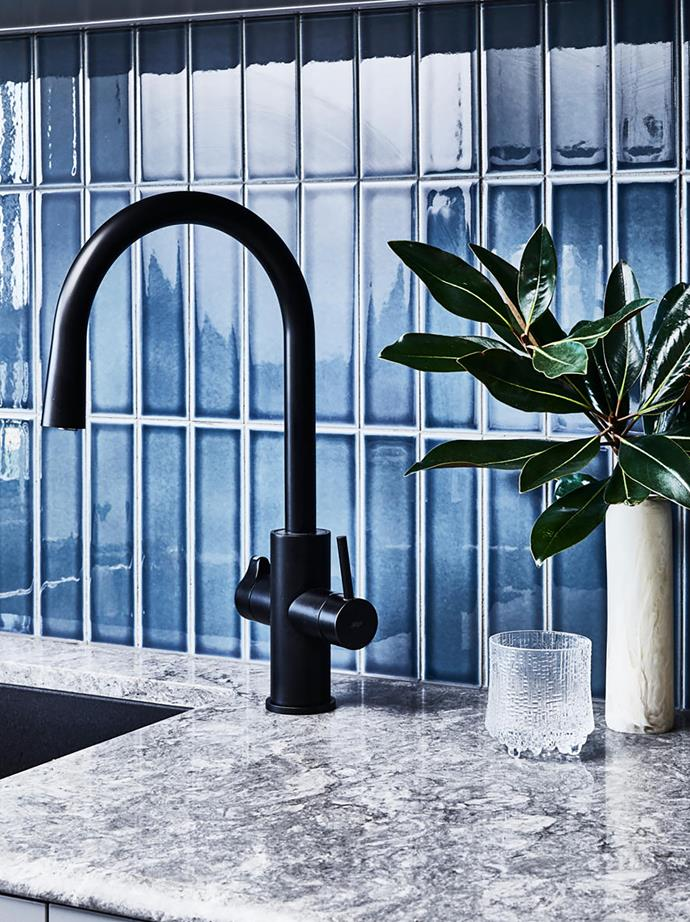 Kitchen bench slab from Caesarstone matched with tiles from Academy Tiles and a Zip HydroTap 'All-In-One Arc'.