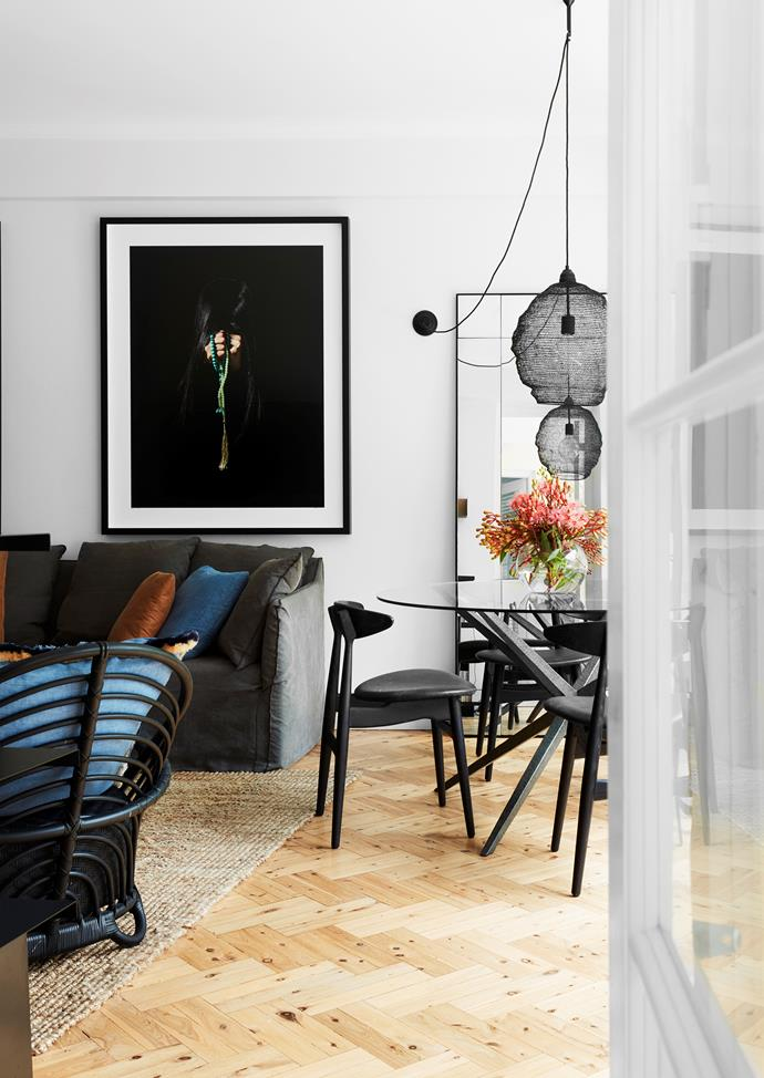 Laura Kincade dining table and pendant light from Les Interieurs reflected in an MCM House mirror. Artwork by Nasin Nasr above a sofa from MCM House and a Sika Design armchair from Domo.