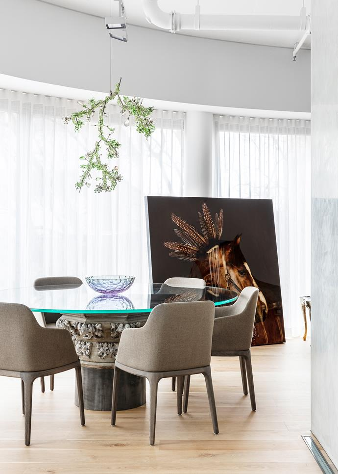 A Todd Boontje-designed Swarovski 'Blossom' chandelier from De De Ce hangs above the dining table from The Country Trader with dining chairs from Poliform. Artwork by Anke Schofield from Aspen Grove Fine Arts.