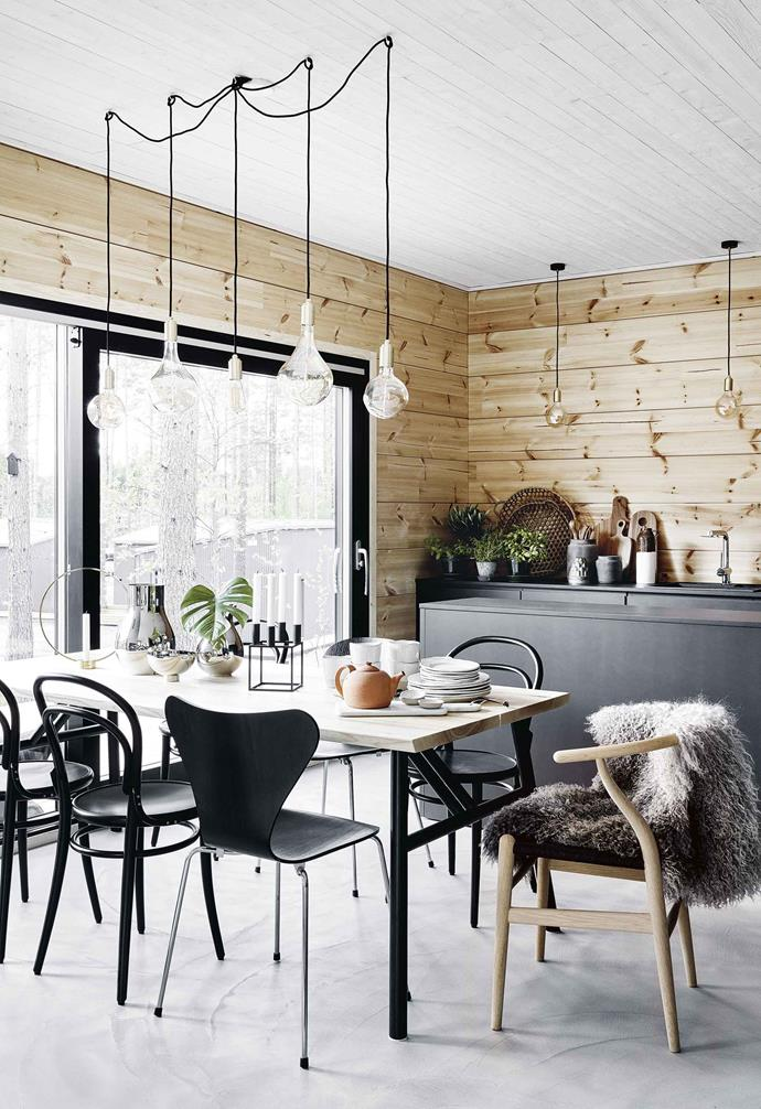 **Dining** The owners of this Finnish house have nailed the modern-cabin vibe and gifted us with lots of clever ideas we'd love to style-souvenir. One of them is having a kitchen so minimal that its sleek black cabinetry reads as a backdrop for the dining table and a match for its mix of designer chairs. The glassy lights above are also clear winners.