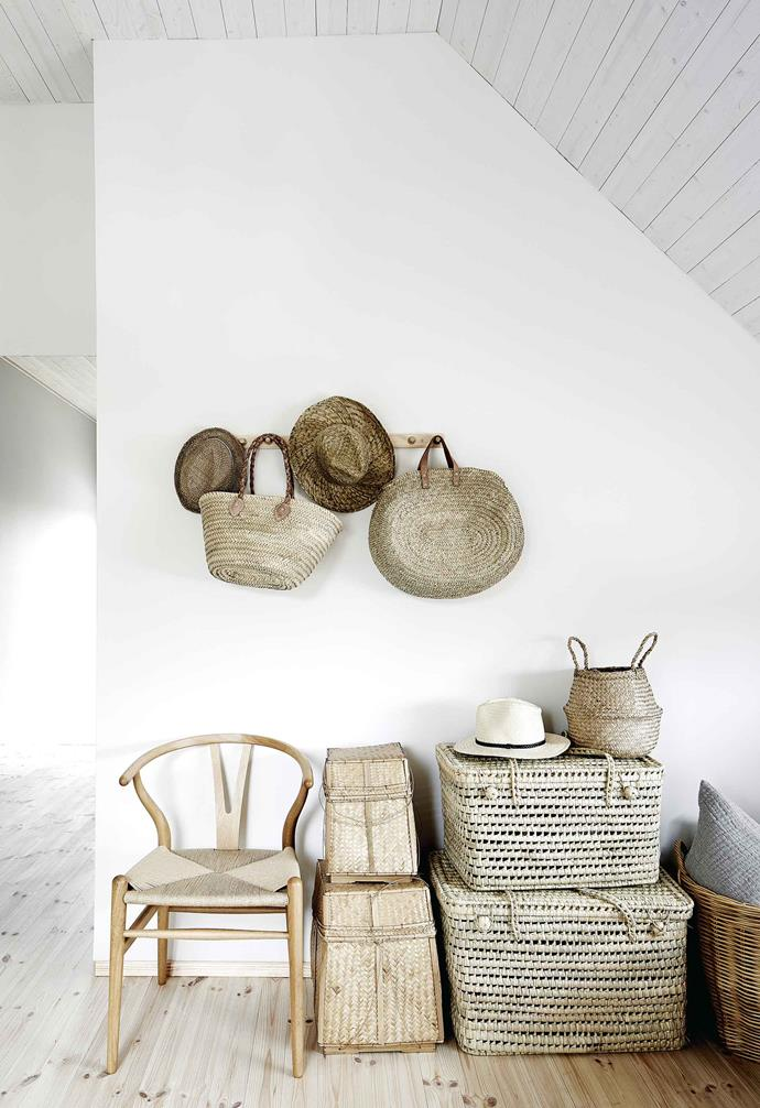 **First-floor hallway** Another Hans Wegner 'Wishbone' chair sits among a pleasing array of rattan baskets and straw hats. The Mustes use the baskets to store bits and bobs.