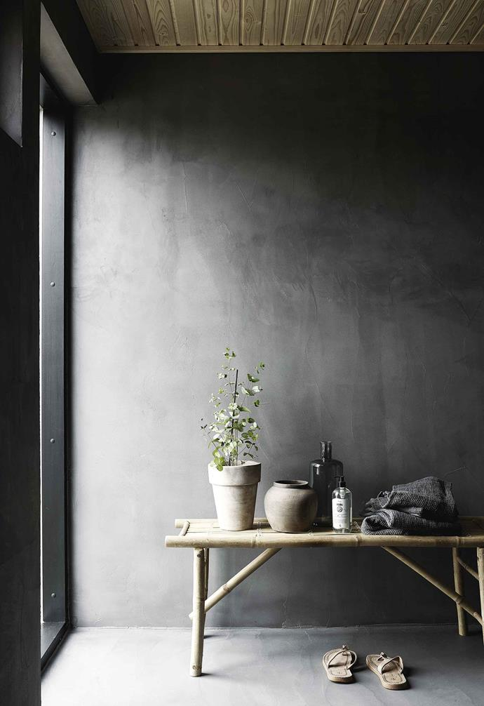 **Corridor** Neutral grey and wood tones highlight the home's life-affirming greenery.