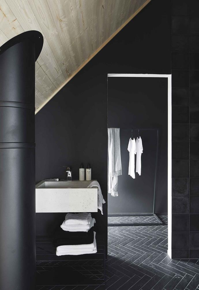 **Ensuite/change area** A discrete gap leads from the bedroom to the ensuite, along glossy herringbone floor tiles. Coal-black walls, raw concrete and modern metallics keep it utterly contemporary. Clothes rack, BEdesign.