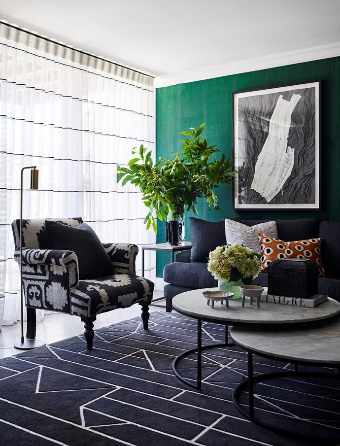 <i>Strata</i> artwork by Hannah Quinlivan hangs against the vivid green Élitis 'Nomades' wallpaper in Sari above a custom 'Belle' sofa from Cosh Living. 'Elle Nest' coffee tables from GlobeWest on a custom 'Hull & Mast' rug.