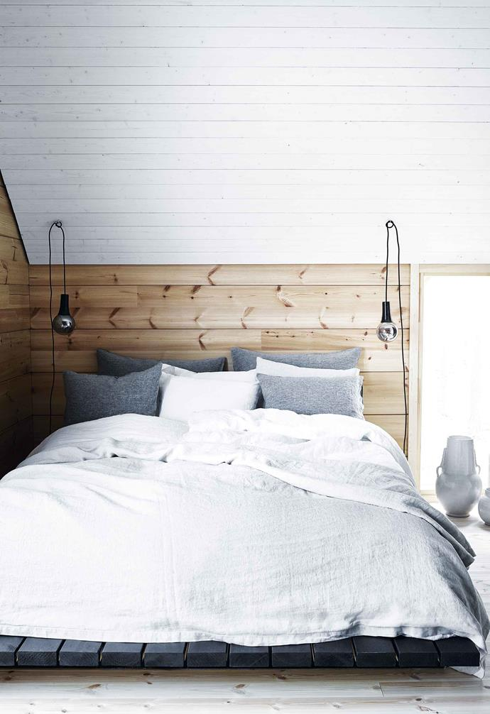 **Main bedroom** Bare timber boards are even more strongly featured upstairs. The Mustes designed their bed to fit snugly under the sloping roof. Chic Balmuir linen brings a boutique-hotel vibe. Side lights by Tala (through LightCo).