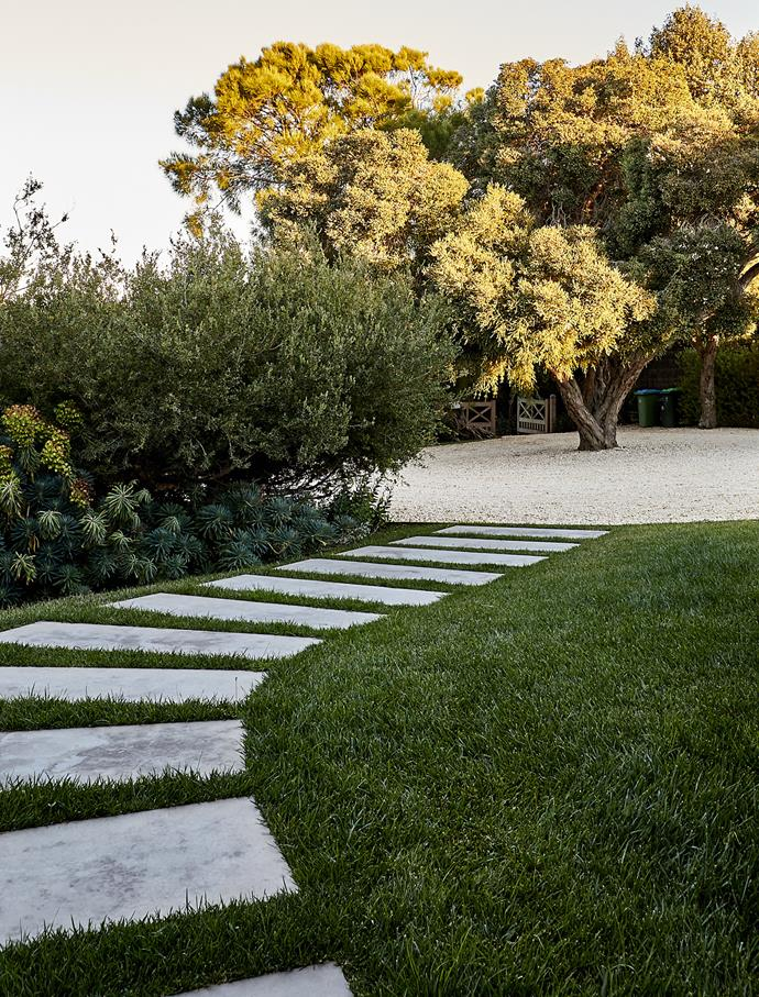 Stepping stones lead from the driveway through lush buffalo lawn.