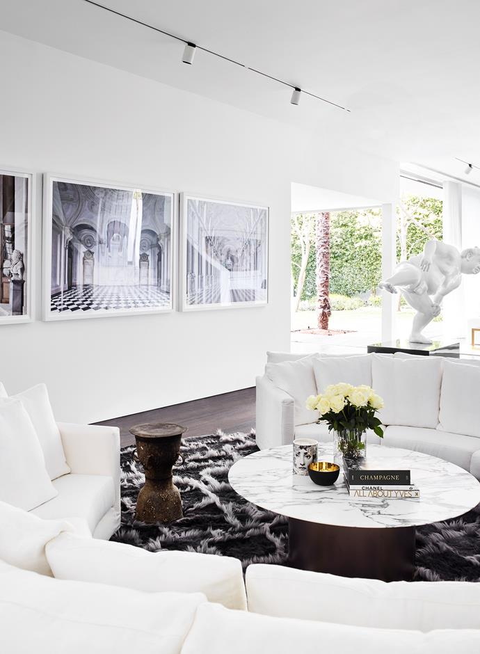 """Although not sunken, the circular white linen sofa is reminiscent of a conversation pit,"" says David Hicks. Photographic artworks by Massimo Listri show perspectives of Italian interiors. Antique Javanese wedding drum used as side table. Custom bronze base Arabescato marble-topped coffee table. Custom sheepskin rug."