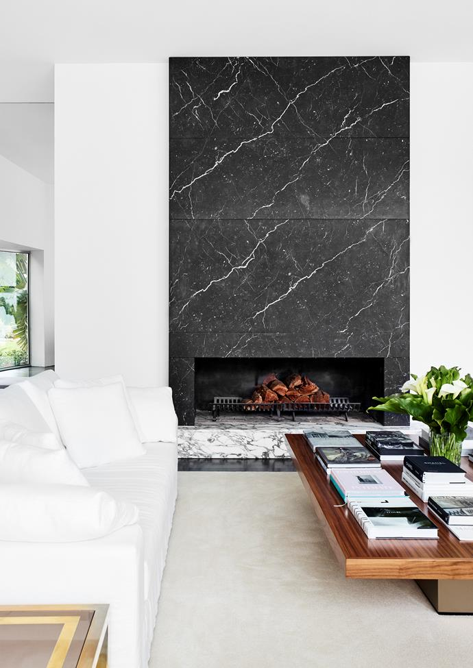 The large custom coffee table is made from walnut timber and takes centrestage, creating a platform on which books, vintage finds and sculpture are displayed. An over-scaled black marble fireplace features a white Arabescato plinth to match the stairs.