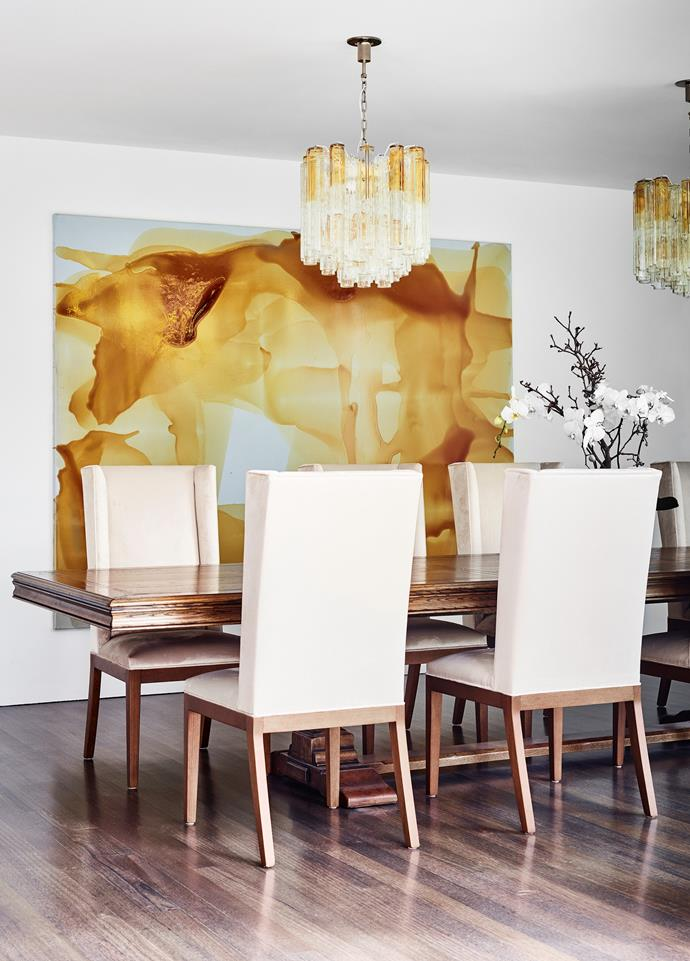 The dining area is in muted walnut and soft caramels. Vintage chandeliers, French table in European oak and custom dining chairs by David Hicks. Orlando Bloom 2 artwork by Dale Frank.
