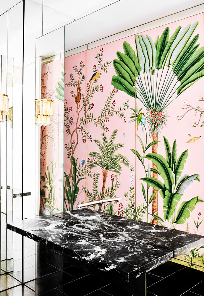 "Hand-painted wallpaper by de Gournay in the powder room inspired by Palm Springs decadence. A cantilevered marble basin extends out from a mirrored wall. Additional mirrors trimmed in thick polished gold were added to reflect the wallpaper panels. Vintage gold wall lights. ""A new black marble floor creates some drama and lifts the room,"" says David Hicks."