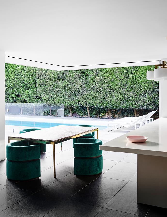 Expanses of operable sliding glass blur the inside with outside. Custom dining table in polished gold and Calacatta Viola tiles. Custom tub chairs in green velvet mimic the lush hedging. Vintage brass chandelier with white parchment shades.