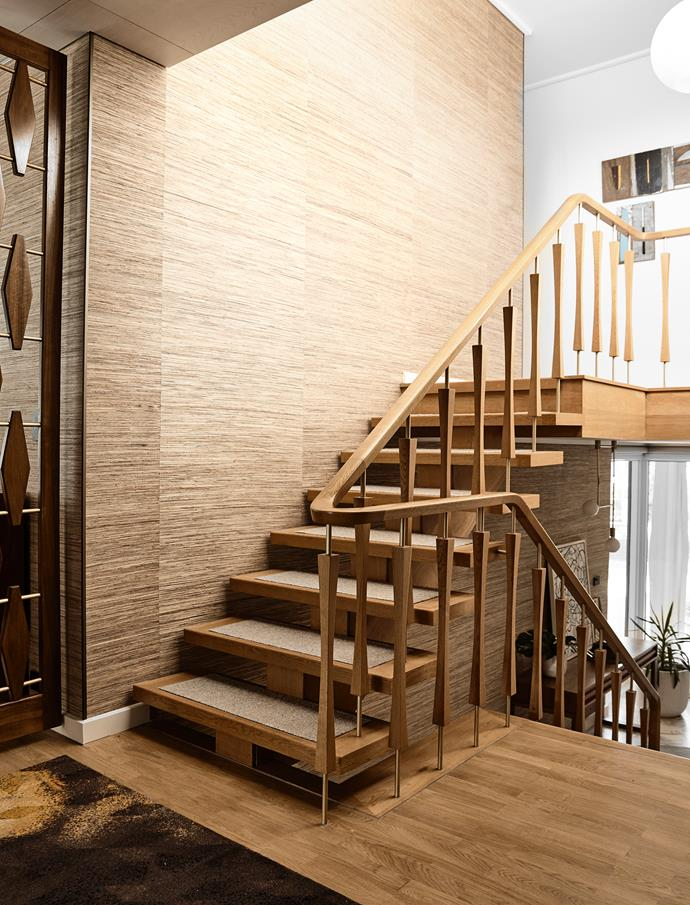 The original American oak stairs have treads inlaid with wool carpet. An anodised gold finish has been added to the balustrades and a series of painted boatyard timber panels by Robert Delves hangs at the top of the stairs.