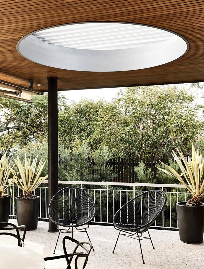 A striking circular Louvretec roof system provides light and shade to the outdoor area, with its original terrazzo tiles. The wire outdoor chairs are vintage pieces.
