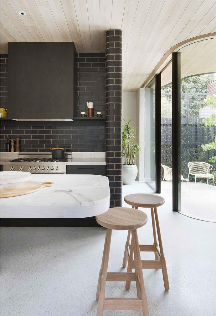 "Visually, the style is set by the newly built garage and [studio](https://www.homestolove.com.au/how-to-create-your-very-own-designer-backyard-room-14767|target=""_blank"") at the back. Inside, the studio is set up as a fourth bedroom with an ensuite for guests, but it may one day serve as a teenagers' hangout, granny flat or home office.<br><br>**Kitchen** Stained oak cabinets by Michael Schiavello and Euroa bricks create a dramatic kitchen, lifted with pale marble benches and Massproductions 'Albert' stools."