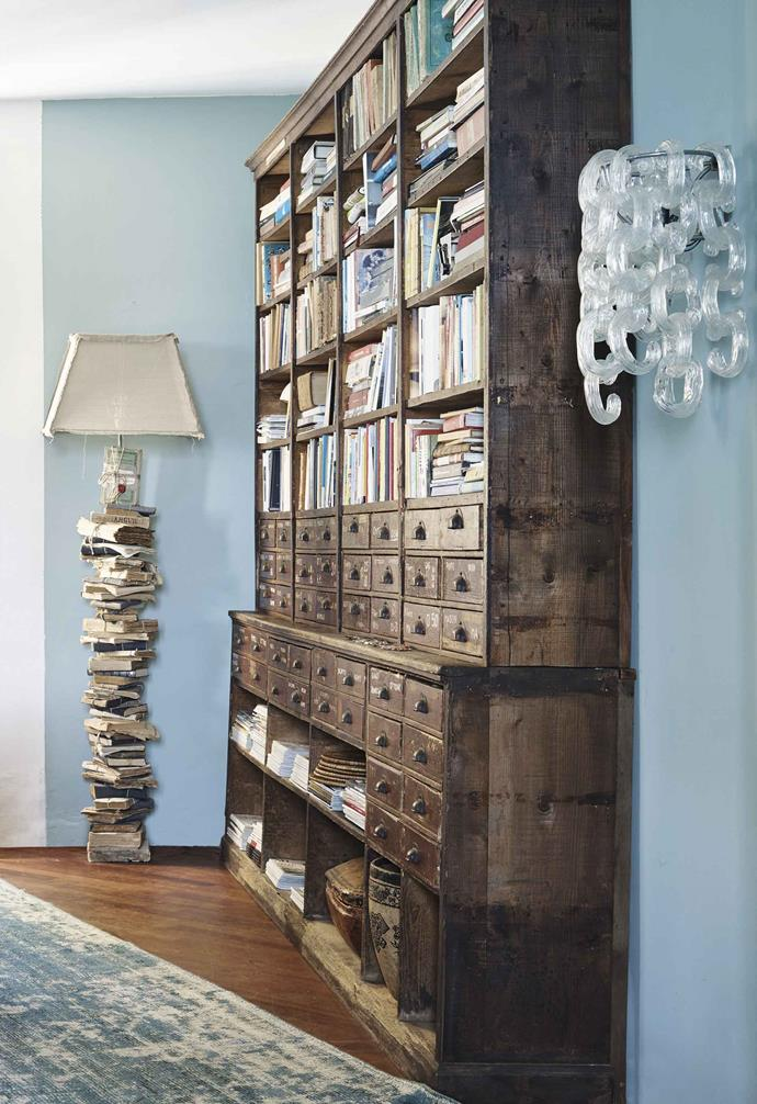 """**Dining room** The bookcase was pulled out of an old hardware store; the standing lamps, made to look like stacks of books, are a popular design sold through [Borgo Delle Tovaglie](https://www.borgodelletovaglie.com/en/