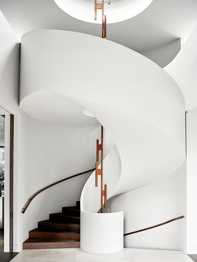 "Architect Rob Mills's signature wraparound staircase makes a grand statement in the entryway of this [luxurious home](https://www.homestolove.com.au/luxurious-home-designed-with-entertaining-in-mind-6733|target=""_blank""). From *Belle* May 2018."