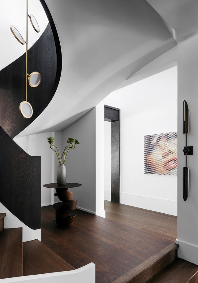 "A custom 'Rachis' table by Dylan Farrell Design for Jean de Merry sits under the sweeping [curve of the staircase](https://www.homestolove.com.au/waterfront-house-nature-inspired-interiors-20420|target=""_blank"") which is clad in ebonised oak. Design by Dylan Farrell Design. From *Belle* June/July 2019."