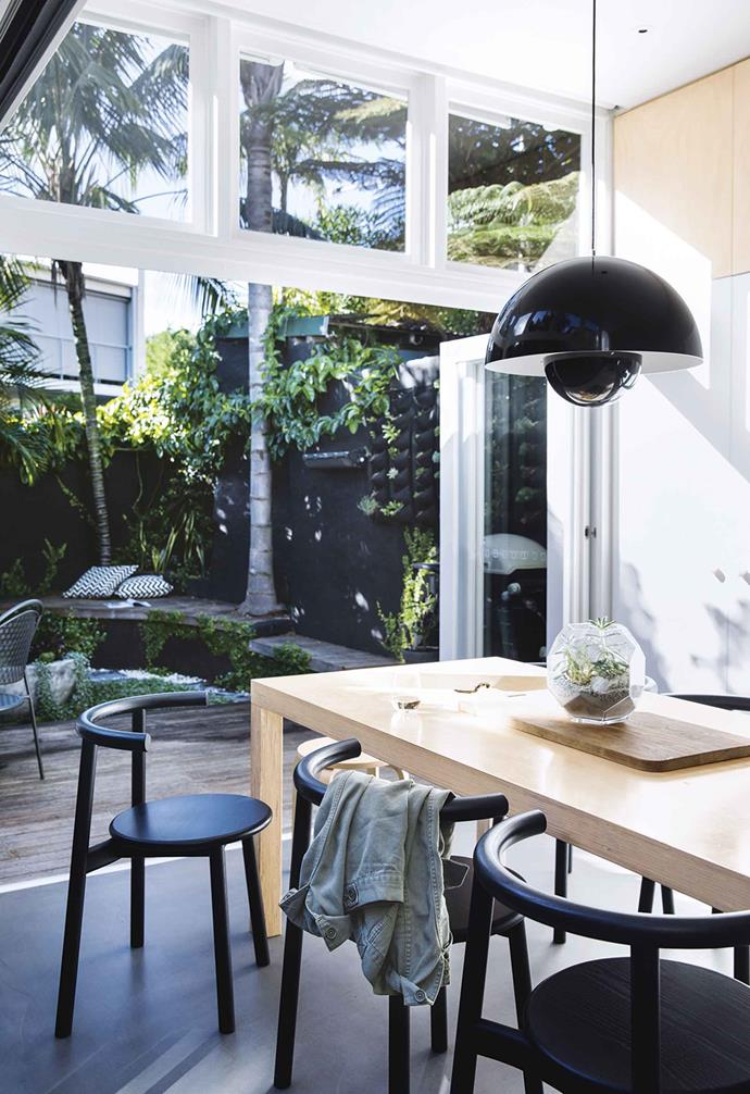 "This [relaxed Paddington terrace](https://www.homestolove.com.au/relaxed-terrace-paddington-18366|target=""_blank"") features white aluminium-framed bifold doors that link the kitchen and dining zone to the outdoor courtyard space. The dining table is joined to the kitchen island, making the most of the home's compact space and maximising the impact of the backyard."
