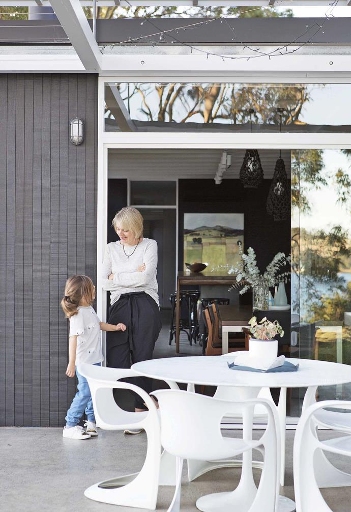 "Glass sliding doors connect the dining area to the outdoor entertaining zone in this [colourful and practical family home](https://www.homestolove.com.au/step-inside-this-colourful-and-practical-family-home-17570|target=""_blank""). The concrete flooring complements the grey painted exterior of the home."