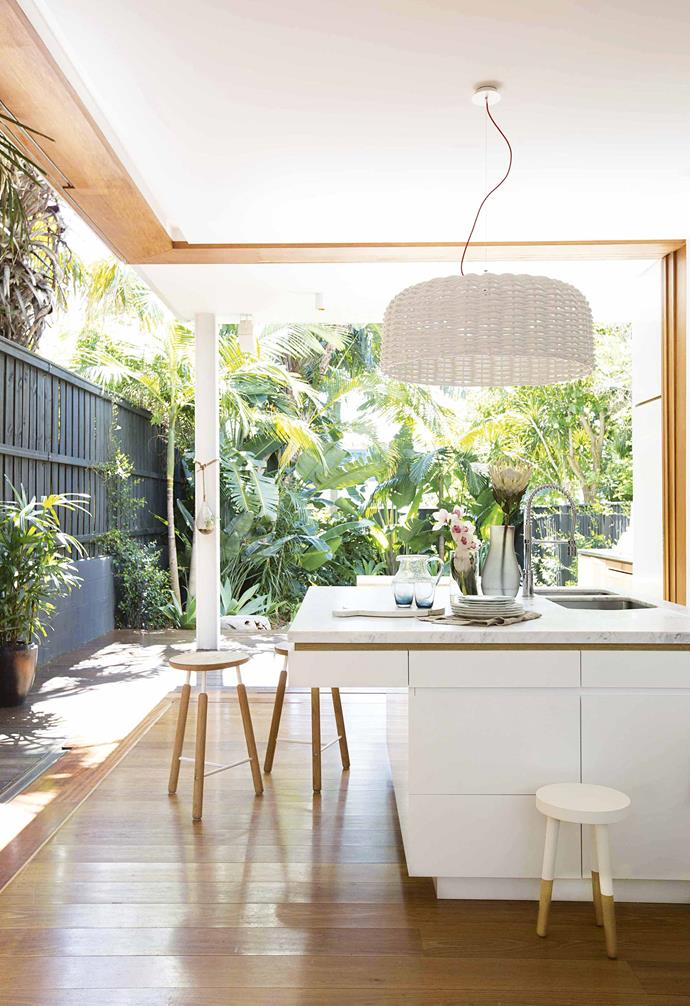 This idyllic kitchen seamlessly connects the indoors with the tropical backyard garden. The Carrara marble bench top and custom-made cabinetry by Martyn Everitt of Make Bespoke Furniture add subtle sophistication to this casual space.