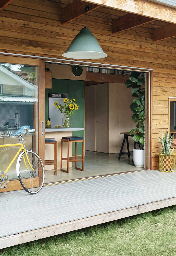 Timber-framed sliding glass doors connect the compact kitchen space in this small eco-friendly home to the outdoor deck and backyard.