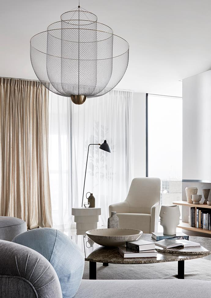 An A Ceramics jug sits atop the Blanche Jelly 'Elna' side table from 1stdibs, alongside the Serge Mouille 'Lampadaire Droit' floor lamp from Cult and Walter Knoll 'Foster 520' high-back armchair from Living Edge.
