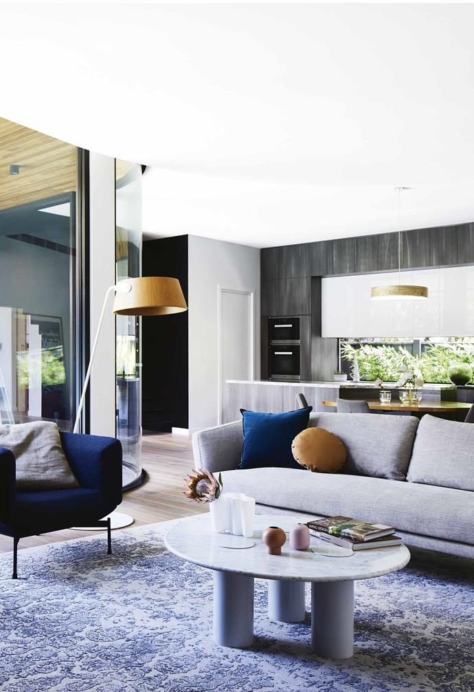 "A curved glass wall allows ample natural light to enter the open-plan living/kitchen/dining space in this [revived Edwardian home](https://www.homestolove.com.au/a-modern-extension-revived-this-century-old-edwardian-home-7147|target=""_blank""). A patterned blue rug demarcates the living area with a grey lounge paired with a velvet blue armchair."