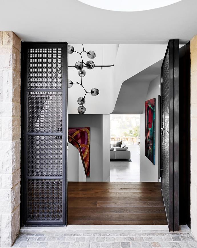 The entrance to the home features a Luigi Rosselli signature mesh door. Lindsey Adelman custom 'Branching' chandelier. Artworks by  Ildiko Kovacs (left) and Dale Frank (right). Tongue n Groove 'Eterno' floorboards in Argento. Walls throughout are painted in Resene 'Quarter Fossil'.