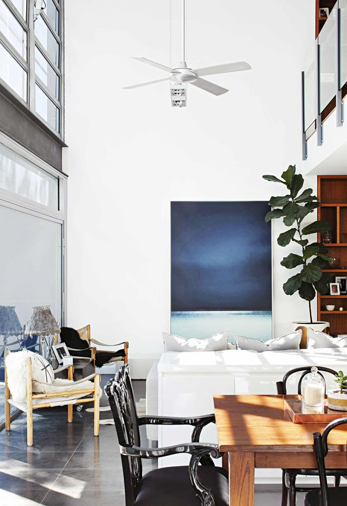 "Light and space has been maximised in this open-plan living area with crisp white walls and floor-to-ceiling windows. A console sits behind the sofa to [divide the living and dining zones](https://www.homestolove.com.au/room-divider-ideas-7914|target=""_blank"")."
