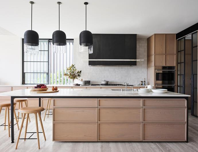 Joinery by Decus Interiors with Calacatta Oro top from WK Stone. 'Indi' pendant lights from Articolo. Mater 'High' stools from Cult. Michaël Verheyden 'Komm' bowl and 'Aperitivo' tray from Ondene. Custom patinated bronze and stone detailed rangehood by Decus Interiors. Wolf 'E Series' oven from Winning Appliances. .