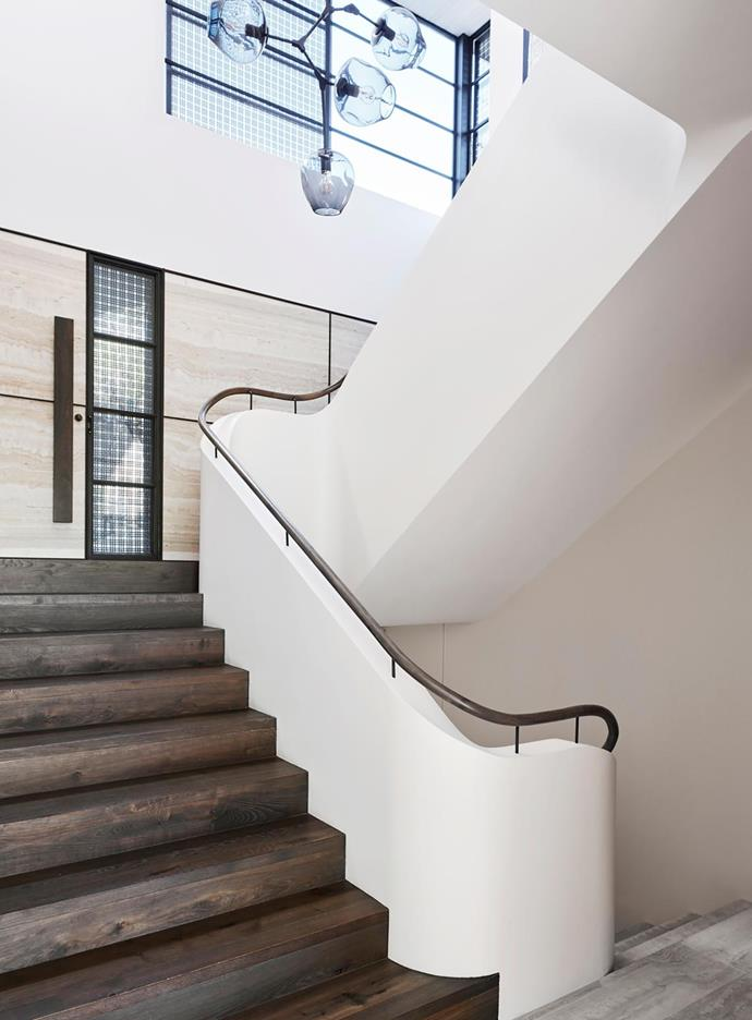 Staircase has a 'Branching' chandelier by Lindsey Adelman. Wall in 'Classic Travertine' from Worldstone. Stairs in 'Eterno Argento' from Tongue n Groove. Custom handrail and balustrade by Decus Interiors