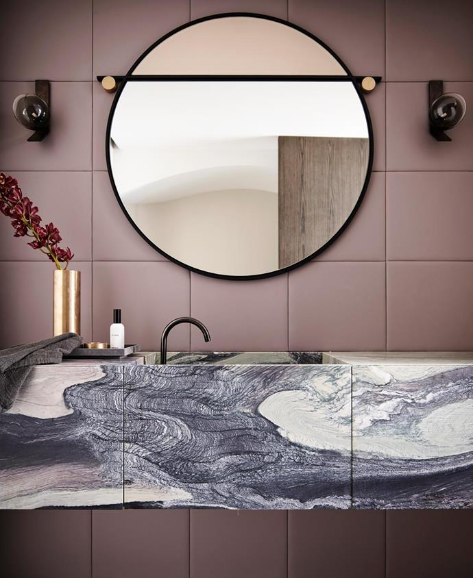 In the powder room, a custom honed Cipollino marble vanity from Granite & Marble Works with Vola brushed black tapware from Candana. Leather wall tiles from Analu. Matter Made 'Abal' mirror from Criteria. Articolo 'Duo' wall sconces. Michaël Verheyden 'Suede Tray' and 'Penne' vase from Ondene.