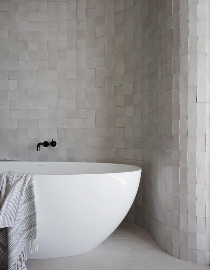 The master ensuite has 'Casa' handmade wall tiles from Onsite and 'Crema Perla' limestone flooring from Bisanna Tiles. Victoria + Albert 'Barcelona' bath with Vola tapware, both from Candana.