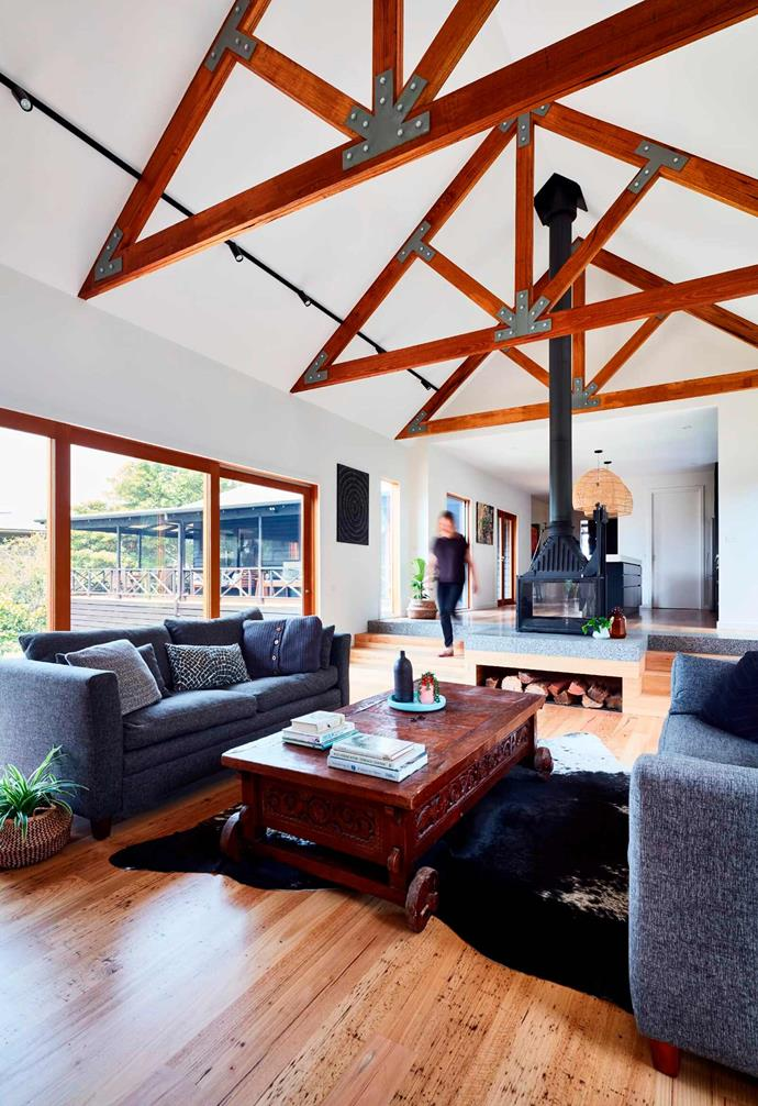 The design of this Mornington Peninsula beach cottage features a generous open-plan living area that naturally connects to the kitchen via a small set of stairs. Timber exposed ceiling beams accentuate the height of the space with a striking statement fireplace marking the beginning and end of the kitchen.