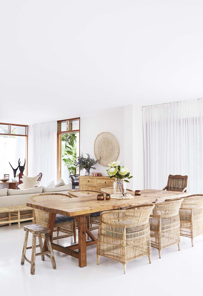 "A low bench sits behind the cosy sofa in the open-plan living and dining space of this [Byron Bay home](https://www.homestolove.com.au/relaxed-all-white-byron-bay-home-with-upcycled-details-19266|target=""_blank"") which features an all-white palette compared with natural timber tones."