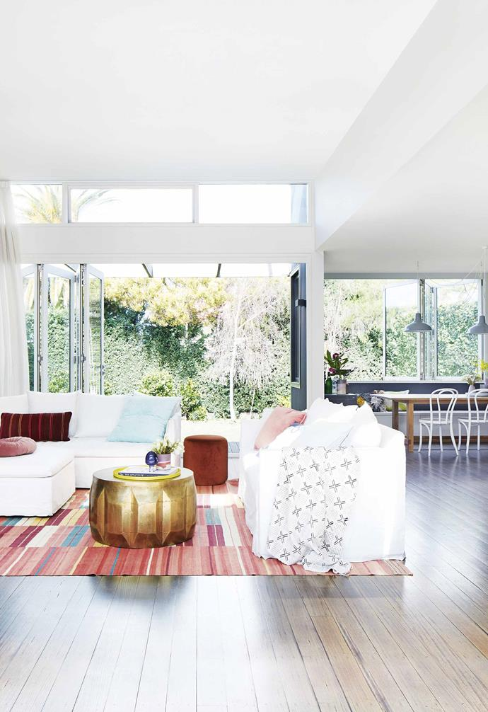 "This [renovated miner's cottage in Geelong](https://www.homestolove.com.au/miners-cottage-renovation-geelong-18479|target=""_blank"") features a colourful patterned rug to mark out the living zone in this open-plan living space. White sectional sofas finish the striking look and are paired with colourful cushions and a statement brass coffee table."