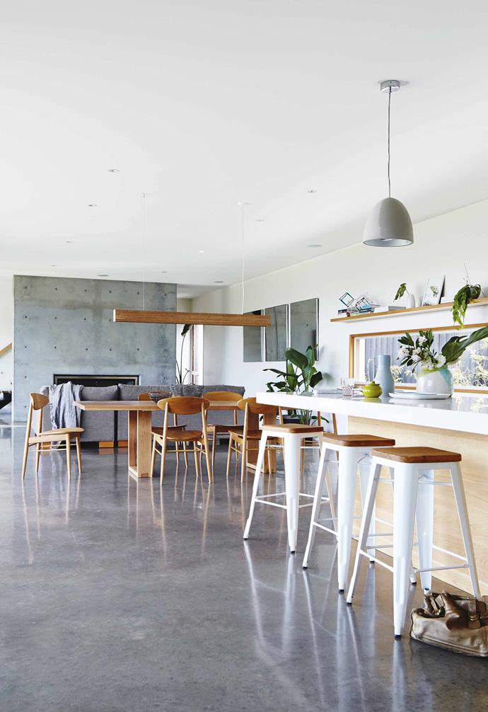"Concrete dominates the design of this [contemporary beachside home](https://www.homestolove.com.au/tour-a-contemporary-beach-side-home-that-mixes-timber-with-concrete-17256|target=""_blank"") and this open-plan living space is no exception to the rule. The timber dining table is paired with a statement timber pendant light to separate the living and kitchen zones."