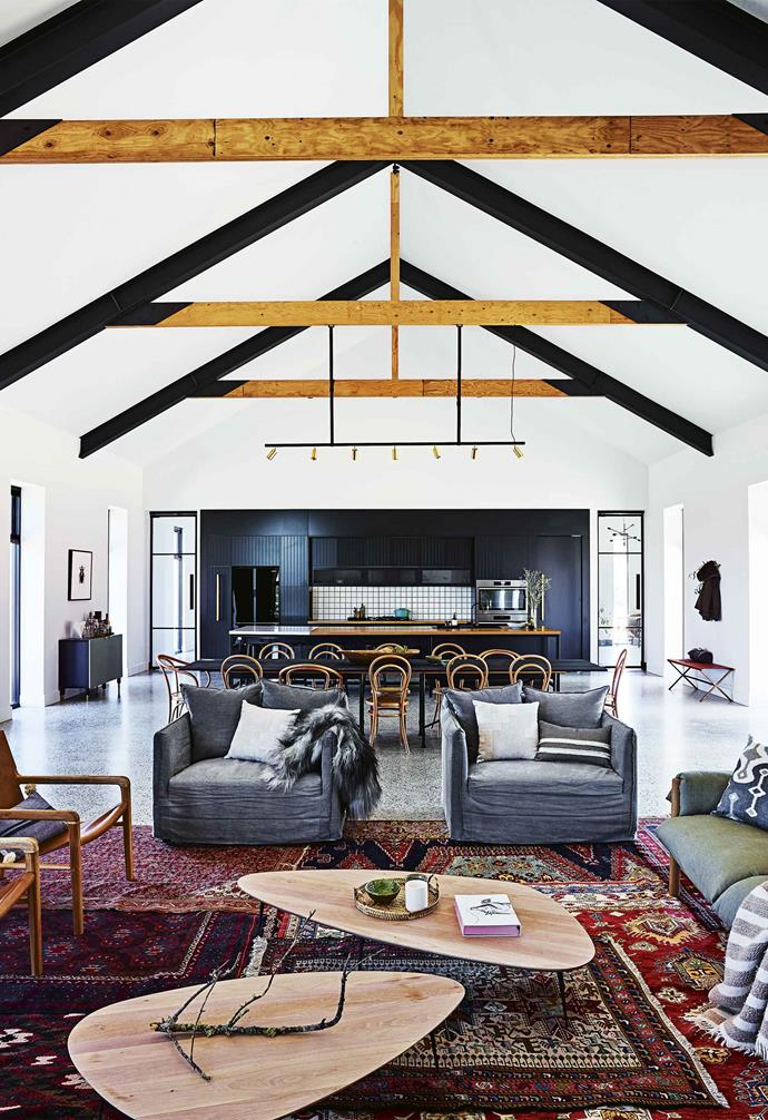 "The design of this [cosy country farmhouse](https://www.homestolove.com.au/country-farmhouse-17468|target=""_blank"") was centred around a large central 'great room' which featured a striking cathedral ceiling, stone fireplace, and a generous open-plan design. The lounging segment of this space features a playful burst of colour by way of multiple layered rugs that also serve to demarcate the area."