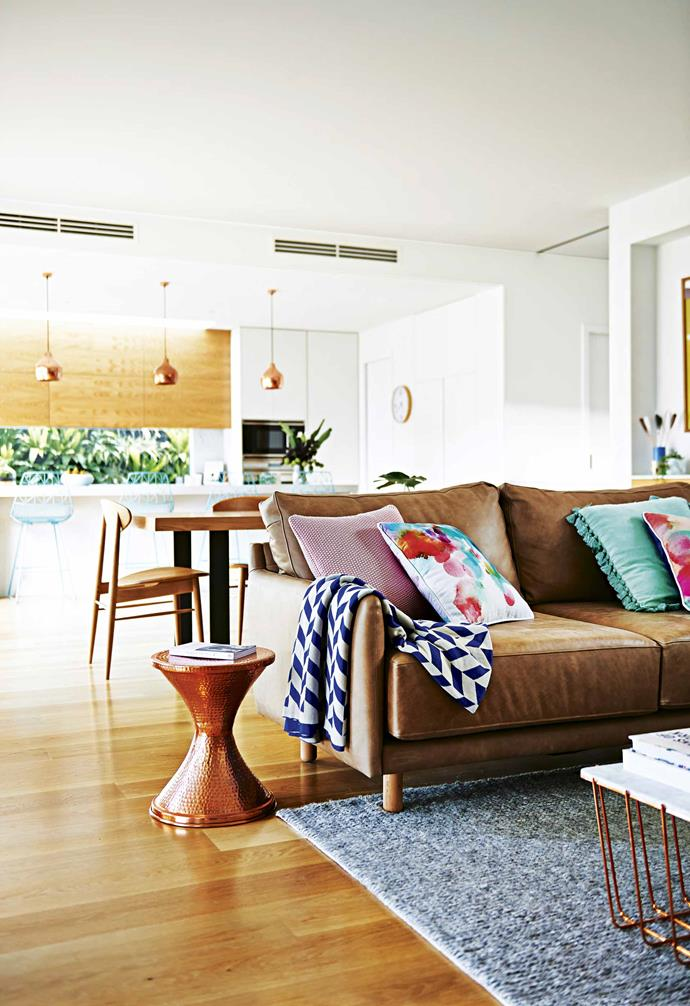"A custom tan leather sofa is paired with a grey rug in the living area of the open-plan living space in this [family-friendly Californian bungalow](https://www.homestolove.com.au/family-friendly-californian-bungalow-18198|target=""_blank""). Behind the living zone sits a simple dining set-up and a generous kitchen."