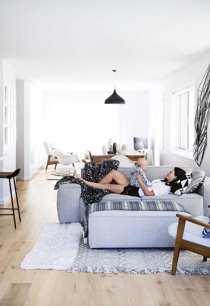 "This [minimalist monochrome apartment](https://www.homestolove.com.au/minimalist-apartment-northern-beaches-17911|target=""_blank"") features a compact open-plan living space with the living area situated next to the kitchen space. The lounge features a modular grey sofa and textured grey rug to create a cosy space."