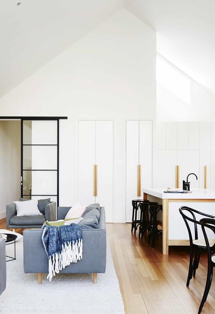 "The open-plan living space in this [Scandi-style home](https://www.homestolove.com.au/scandi-style-glass-house-extension-17515|target=""_blank"") packs a mighty punch with ample storage. The living space is demarcated with a large grey rug and grey sofas, while the kitchen is oriented towards the outdoor entertaining spaces."