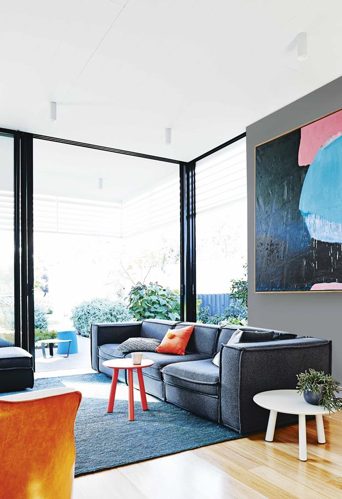 """When Mardi suggested an orange goat-hair carpet on the stairs, Jen and I raised our eyebrows but now we love it,"" says Doug. ""The graphic blue paint feature on the sliding door may have been seen as risky but we think it's beautiful.""<br><br>**Living area** Much of the home's furniture is from [Jardan](https://www.jardan.com.au/